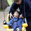 Father pushing disabled son on handicap swing — Stock Photo #11616751
