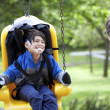 Father pushing disabled son  on handicap swing — Stock Photo
