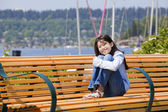 Ten year old girl enjoying the sun on bench by the lake — Stock Photo