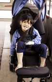 Disabled little preschool boy in wheelchair on bus — Stock Photo