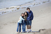 Three siblings together on the beach — Stock Photo
