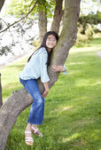 Young girl resting on a tree branch — Stock Photo