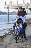 Father pushing wheelchair with disabled son on beach — Stock Photo
