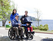 Family with disabled senior and child walking outdoors — Stock Photo