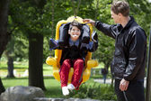 Father pushing disabled boy in special needs swing — Foto de Stock