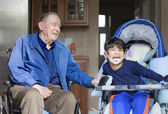 Elderly man in wheelchair laughing with disabled boy in kitchen — Stock Photo
