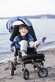 Happy disabled boy in wheelchair on the beach — Stock Photo