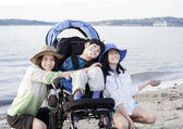 Sisters taking care of disabled brother on beach — Stock Photo