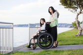 Taking care of sister in wheelchair by beach — Stock Photo