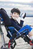 Happy disabled five year old boy in wheelchair on the beach — Stock Photo