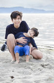 Big brother holding disabled boy on beach — Stock Photo