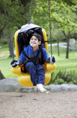 Father pushing disabled son on handicap swing — Stockfoto