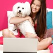 Happy teenager sitting in her bed with her white dog — Stock Photo #11089761
