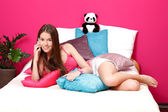 Beautiful teenager making a call in her pink room — Stock Photo