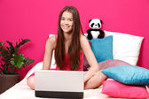Teenager smiling and using laptop — Stock Photo