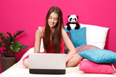 Brunette teenager reading her emails on her laptop — Stock Photo