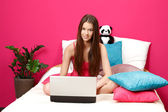 Nice brunette teenager sitting in her room and using laptop — Stock Photo