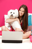 Happy teenager sitting in her bed with her white dog — Stock Photo