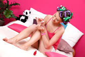 Young manicurist applying red nail polish on her nails — Stock Photo