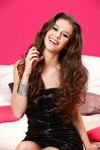 Portrait of a beautiful brunette teenager spraying perfume bottl — Stock Photo