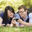 Stok fotoğraf: Young Couple at Park Texting Together