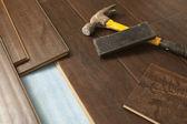 Hammer und block mit neuen laminatböden — Stockfoto