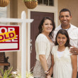 Постер, плакат: Hispanic Family in Front of Their New Home with Sold Sign