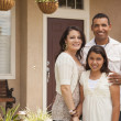 Stock Photo: Small Hispanic Family in Front of Their Home