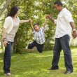 Hispanic Mother and Father Swinging Son in the Park — Stockfoto
