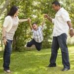 madre hispana y padre hijo hace pivotar en el parque — Foto de Stock