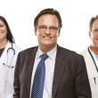 Businessman with Medical Personnel Behind — Stock Photo #11470733