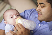 Happy Hispanic Father Bottle Feeding His Son — Stock Photo