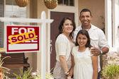 Familia hispana frente a su nuevo hogar con cartel vendido — Foto de Stock