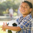 Mixed Race Boy Holding Soccer Ball in the Park Against Tree - Stockfoto