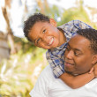 Mixed Race Father and Son Playing Piggyback - Stock Photo
