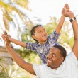 Mixed Race Father and Son Playing Piggyback - Foto Stock