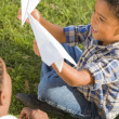 Mixed Race Father and Son Playing with Paper Airplanes - Stock Photo