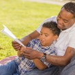 Mixed Race Father and Son Playing with Paper Airplanes — Stock Photo #11584943