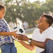 Father Hands New Soccer Ball to Mixed Race Son — Stock Photo