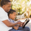 Mixed Race Father and Son Using Touch Pad Computer Tablet - Foto de Stock