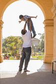 African American Father Lifting Mixed Race Son in the Park — Stock Photo