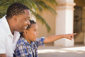 Mixed Race Father and Son Pointing in the Park — Stock Photo