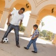 Mixed Race Father and Son Playing Soccer in the Courtyard - Stockfoto
