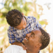 Mixed Race Father and Son Playing Piggyback in Park - Stock Photo