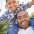 Royalty-Free Stock Photo: Mixed Race Father and Son Playing Piggyback in Park