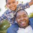 Mixed Race Father and Son Playing Piggyback in Park — Stock Photo #11634506
