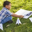 Mixed Race Boy Learning How to Fold Paper Airplanes - Stock Photo