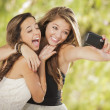 Attractive Mixed Race Girlfriends Taking Self Portrait with Came - Stock Photo