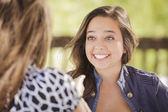 Aantrekkelijke vriendinnen lachen vergadering buiten — Stockfoto