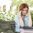Stock Photo: Female Student Outside with Headache Sitting with Books and Back